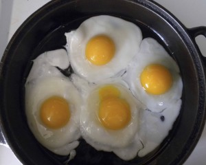 Sheri's pastured eggs frying in cast iron pan