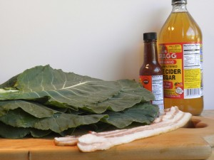 Ingredients for traditional collard greens with natural bacon, organic hot sauce, and unfiltered organic apple cider vinegar.
